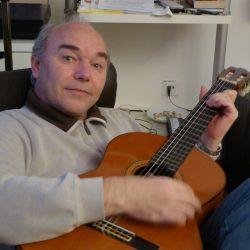 Reinhard Friedrich sitzend mit Gitarre in der Hand