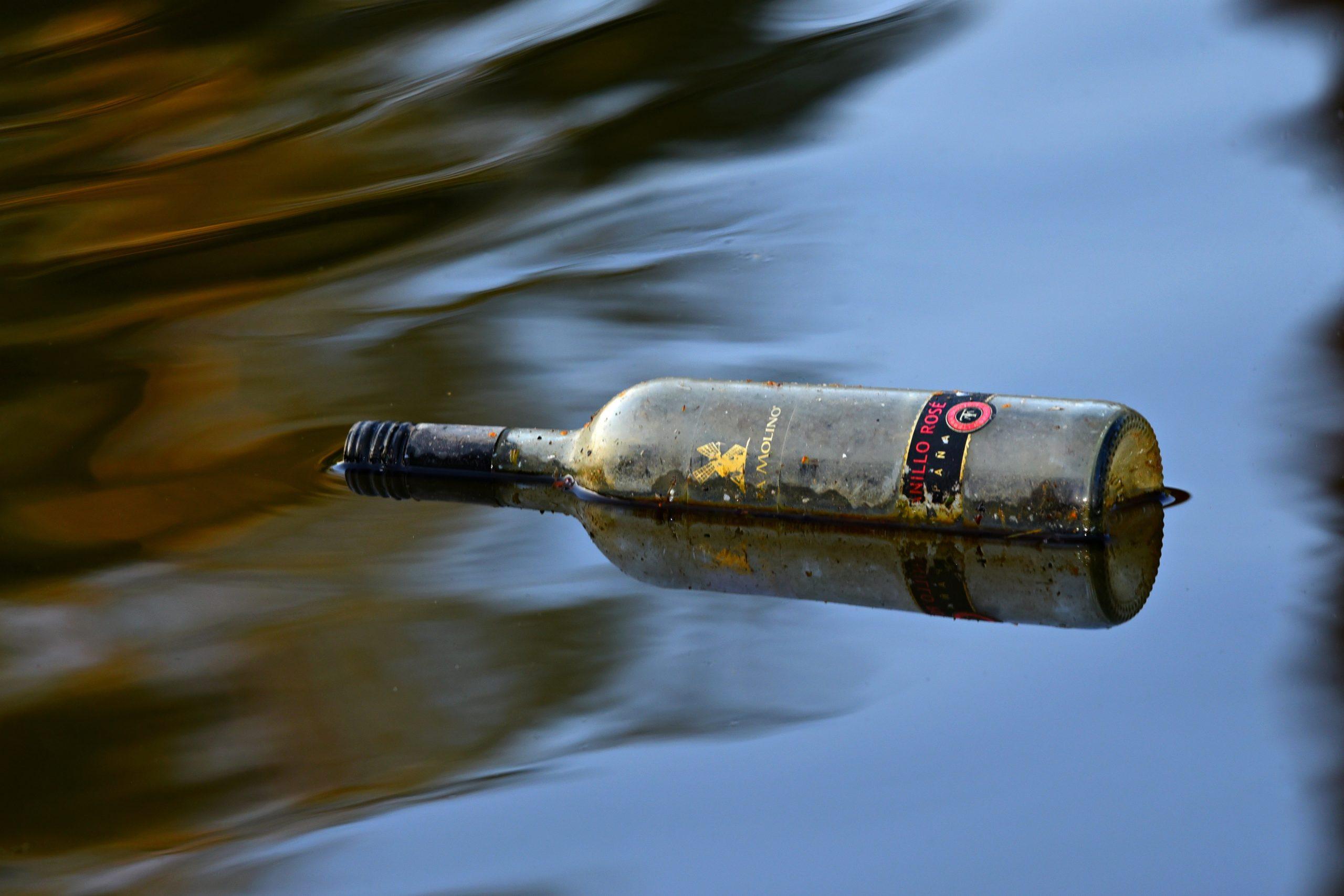 leere Weinflasche schwimmt in einem See